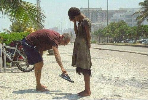 Un homme donne ses sandales à une sdf à Rio (Bresil)